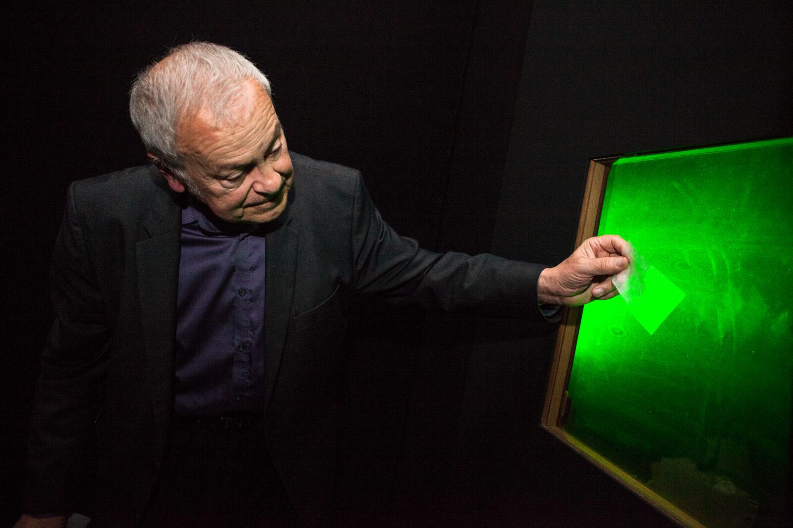 Gilbert Tribillon montre à l'aide d'un papier calque la zone de netteté d'une image holographique.
